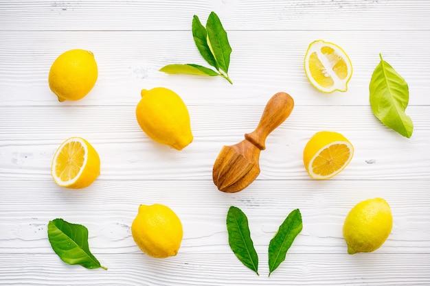 Limones frescos y hojas de los limones en el fondo de madera blanco.