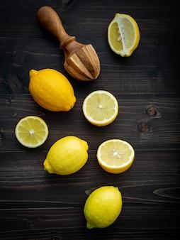 Limones frescos y hojas de los limones en fondo de madera lamentable.
