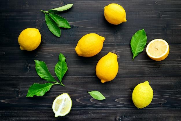 Limones frescos y hojas de los limones en el fondo de madera oscuro.