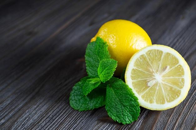 Limones frescos y hojas de menta en la mesa de madera oscura.