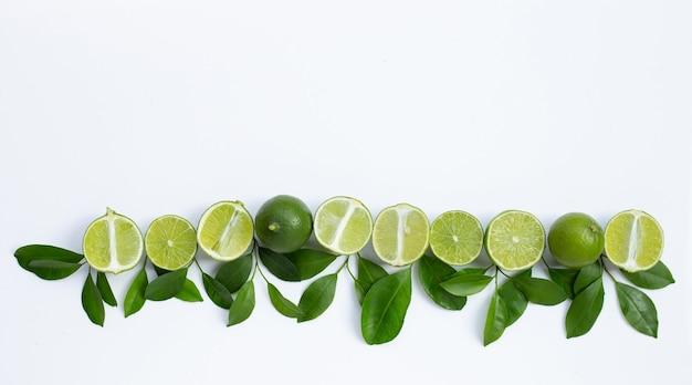 Limones frescos con hojas verdes sobre fondo blanco. vista superior