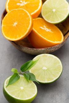Limones de frutas cítricas mixtas, naranja, kiwi, limas sobre una mesa gris.