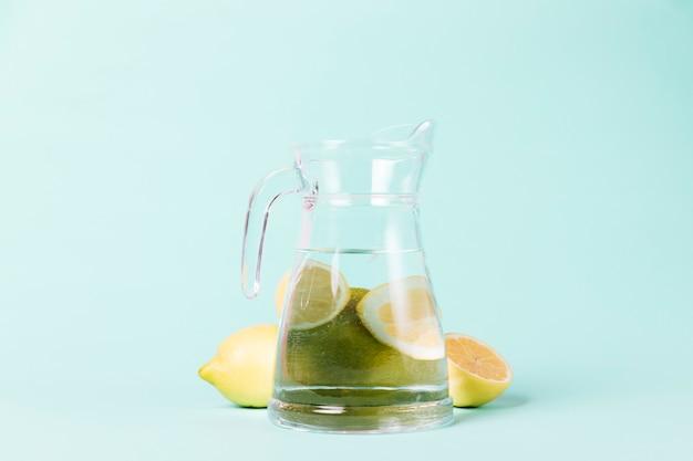 Limones y jarra sobre fondo azul.