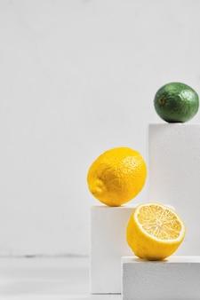 Limones y limas frescas en mesa gris, concepto minimalista con frutas cítricas