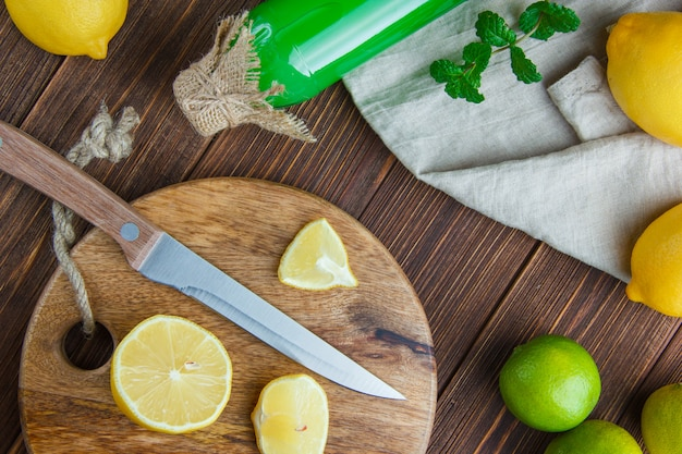 Limones con limas, hojas, cuchillo, bebida, tabla de cortar en madera y papel de cocina, plano.