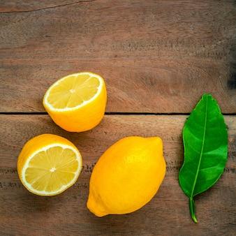 Limones y limones frescos hojas sobre fondo de madera rústica.