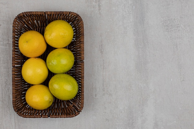 Limones maduros frescos en cesta de madera.