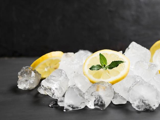 Limones con menta y pila de cubitos de hielo.