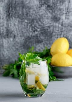 Limones y menta en un recipiente con agua helada de desintoxicación vista lateral sobre grunge y superficie gris