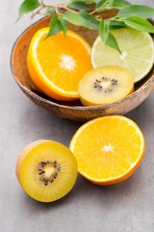 Limones mezclados de cítricos, naranja, kiwi, limas sobre un fondo gris.