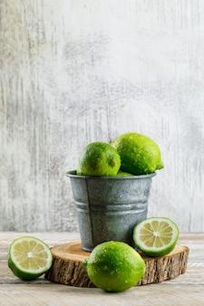 Limones en un mini cubo con vista lateral de tabla de cortar en madera y sucio
