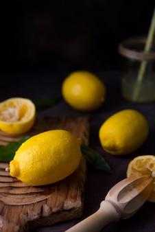 Limones orgánicos jugosos maduros sobre una tabla de madera, fondo oscuro, cerrar