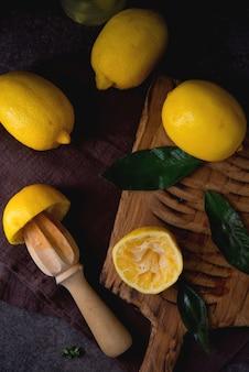 Limones orgánicos jugosos maduros sobre una tabla de madera, fondo oscuro, vista superior