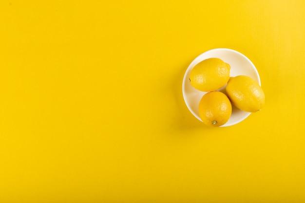 Limones en un plato blanco sobre amarillo