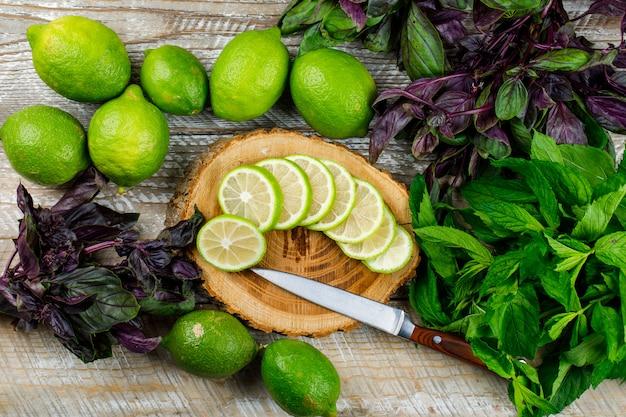Limones con racimos de albahaca, cuchillo en madera y tabla de cortar, aplanada.