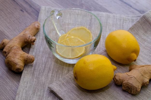 Limones y raíces de jengibre en gris como tratamiento contra la gripe estacional