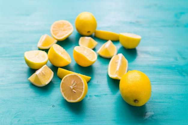 Limones recién cortados y enteros en tablas rústicas de color aguamarina. concepto de verano, vitaminas y frescura.