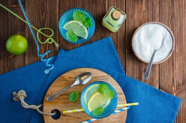 Limones en un recipiente con tela azul, cuchillo de madera y una botella de jugo, pajitas, tazón de fuente de sal vista superior sobre una superficie de madera