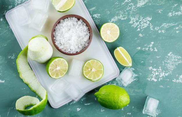 Limones con sal, cubitos de hielo sobre yeso y tabla para cortar,