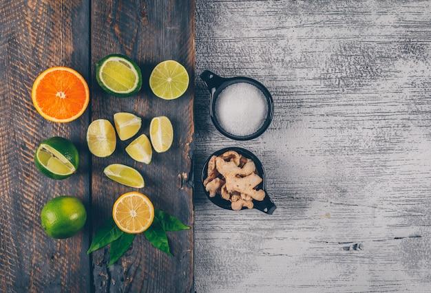 Limones verdes y amarillos y naranja con tazas de sal y jengibre vista superior en una bandeja de madera y fondo de madera gris
