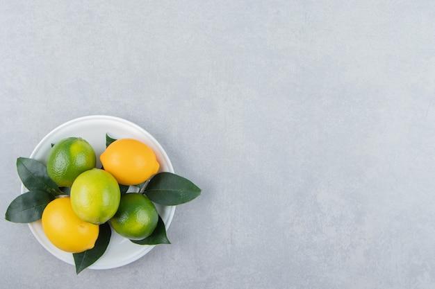 Limones verdes y amarillos en la placa blanca.