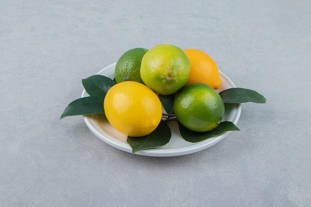 Limones verdes y amarillos en un plato blanco.