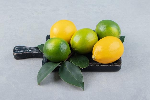 Limones verdes y amarillos sobre tabla de cortar negra.