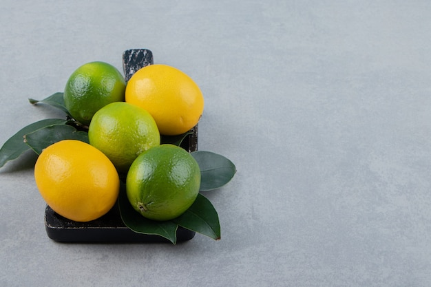 Limones verdes y amarillos sobre tabla de cortar negra