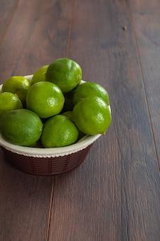 Limones verdes en cesta en mesa marrón