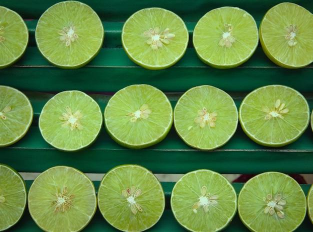 Limones verdes en rodajas frescas o fondo de cal.