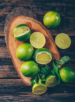 Limones verdes con rodajas y hojas planas sobre una rodaja de madera y fondo de madera oscura.
