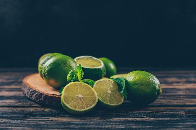 Limones verdes con rodajas y hojas de vista lateral en una rodaja de madera y espacio de fondo de madera oscura para texto