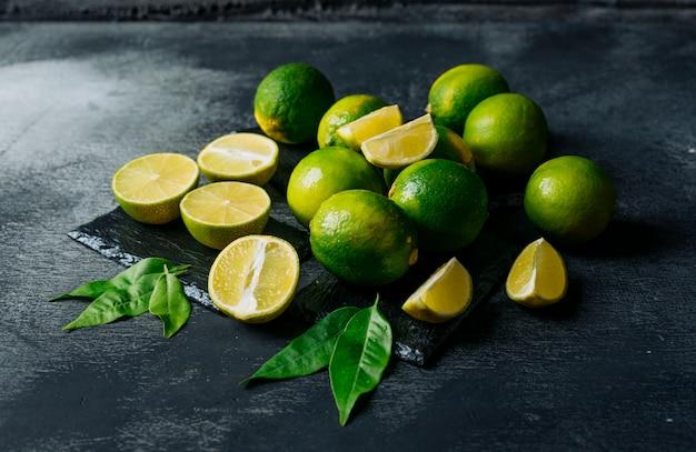 Limones verdes con rodajas vista de ángulo alto sobre un fondo negro con textura