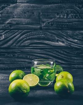 Limones verdes en un vaso de agua con rodajas vista lateral en un espacio de fondo negro con textura para texto