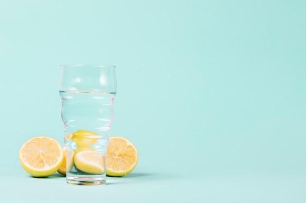 Limones y vidrio sobre fondo azul.