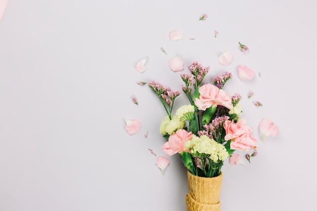 Limonium y flores de los claveles en los conos de la galleta aislados en el fondo blanco