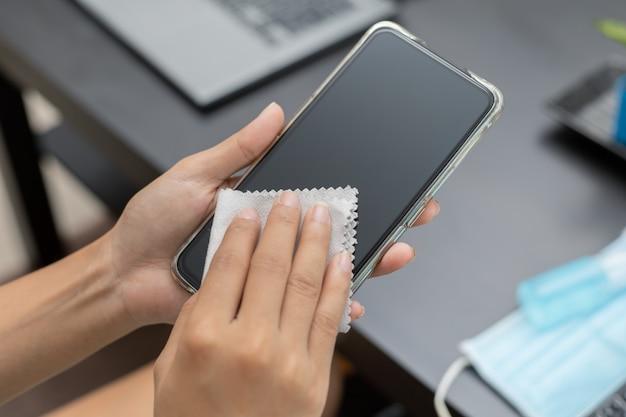 Se limpia la mano de la mujer del teléfono móvil con un paño y alcohol para eliminar virus y gérmenes dañinos.