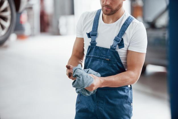 Limpia las manos del aceite. empleado en el uniforme de color azul trabaja en el salón del automóvil