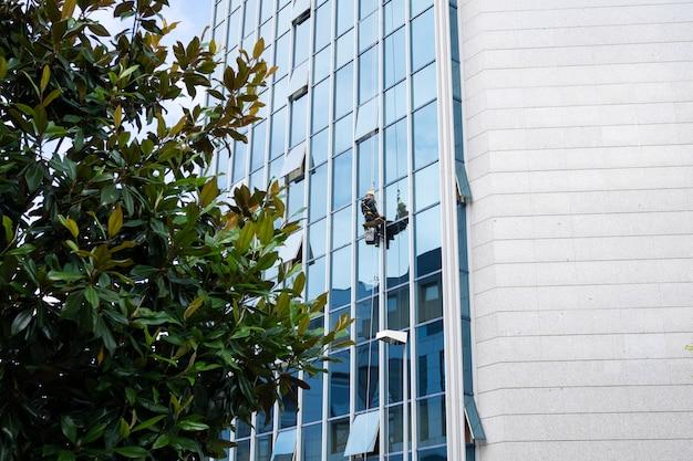 Limpiacristales trabajando en una fachada de vidrio suspendida