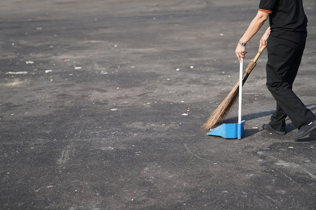 El limpiador barre la basura en una gran área exterior de asfalto al mediodía.