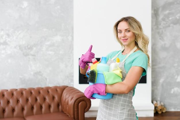Limpiador femenino gesticular pulgar de pie en casa con productos y herramientas de limpieza