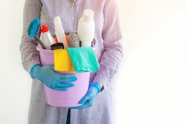 Limpiador femenino sosteniendo un cubo con productos de limpieza.