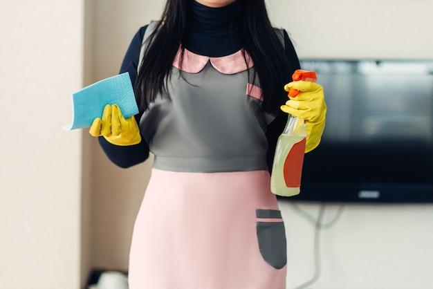 Limpiador femenino en uniforme y guantes tiene equipo de limpieza en las manos, interior de la habitación del hotel.