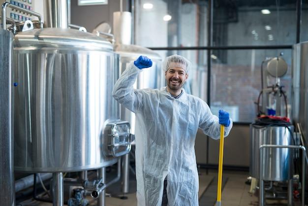 Limpiador industrial profesional en ropa de trabajo de protección sonriendo y sosteniendo el puño en alto en la planta de producción