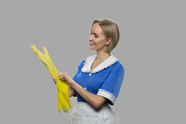 Limpiador de mujer alegre se pone guantes. la criada sexy sonriente en uniforme azul está lista para trabajar.