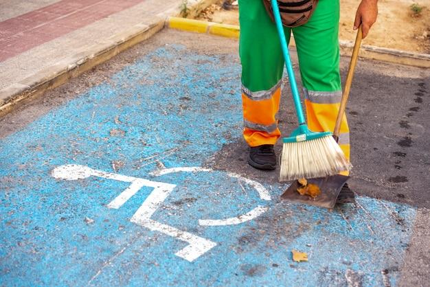 Limpiador profesional barriendo las calles de la ciudad, con una canasta para tirar la basura que recoge