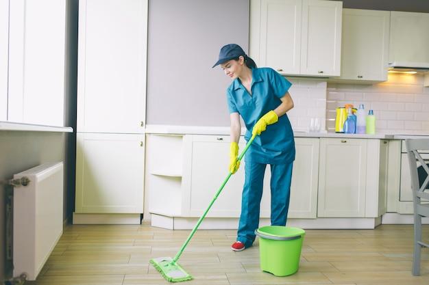 El limpiador profesional lava el piso con un trapeador verde
