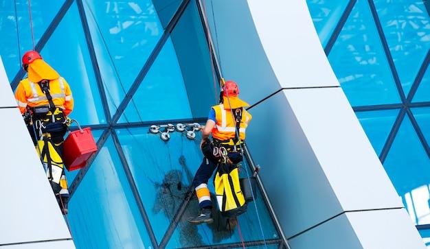 El limpiador de ventanas trabajando en un rascacielos moderno de fachada de vidrio