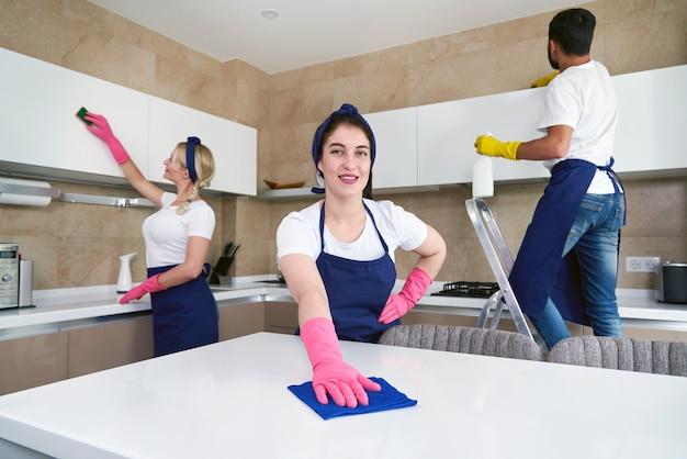 Limpiadores profesionales en uniforme azul lavando el piso y limpiando el polvo de los muebles del living del departamento. concepto de servicio de limpieza