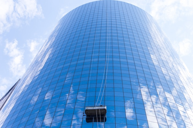 Limpiadores que lavan las ventanas de los rascacielos modernos